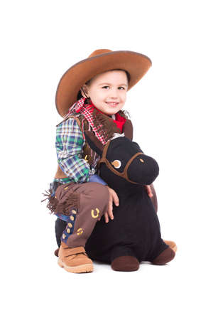 Smiling little cowboy posing on the toy horse. Isolated photo