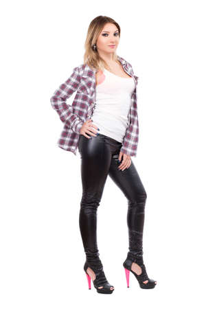 Alluring blonde wearing checked shirt and black pants. Isolated on white photo