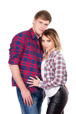 Handsome man and pretty blond woman posing in checked shirts. Isolated on white photo