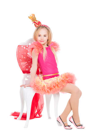 Little girl wearing candy costume sitting on a chair. Isolated