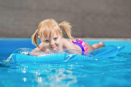 Beautiful little girl swimming on air mattress in water pool