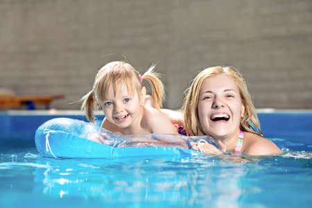 Attractive little girl and her mother swimming in water pool photo
