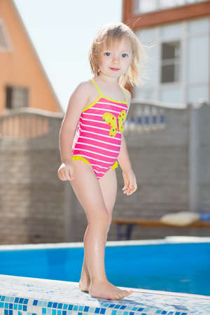 Adorable little girl posing near water pool photo
