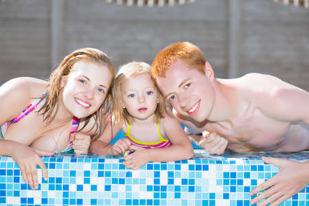 Nice positive family posing in the water pool photo