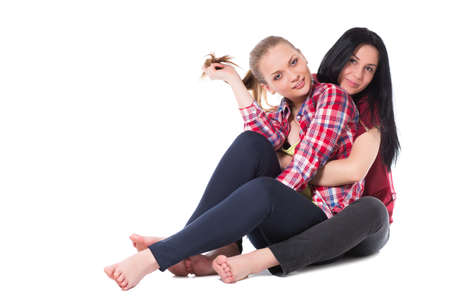 Two pretty girlfriends sitting on the floor. Isolated photo