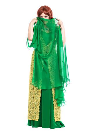 enigmatic: Enigmatico giovane donna che indossa abito verde di lusso. Isolati su bianco