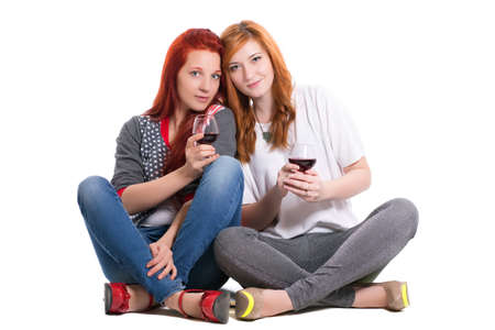 Two redhead women sitting cross-legged with glasses of wine. Isolated on white
