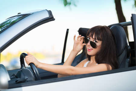 Young smiling brunette posing in grey car with sunglasses Stock Photo