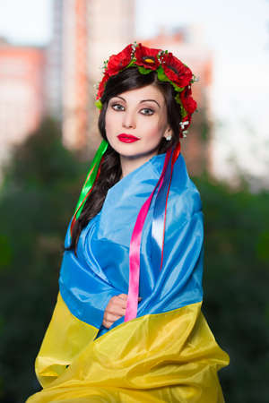 Pretty Ukrainian woman posing wrapped in the flag photo