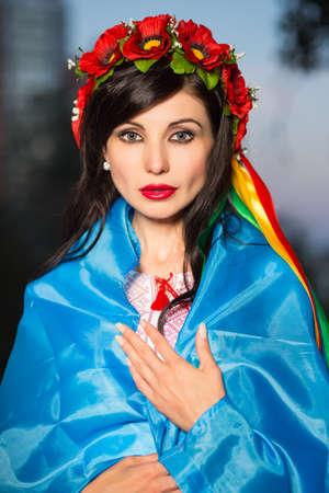 Pretty Ukrainian brunette in poppy wreath posing outdoors photo