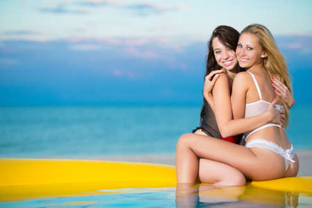 Two playful women hugging each other on the beach at sunset
