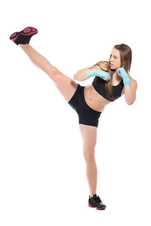 Young sporty woman showing high kick. Isolated on white