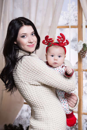 mother and baby deer: Beautiful woman posing with her baby dressed in red antlers