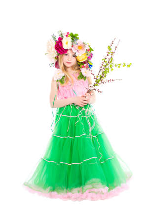 Little girl in wreath on her head posing with flowering branches. Isolated photo