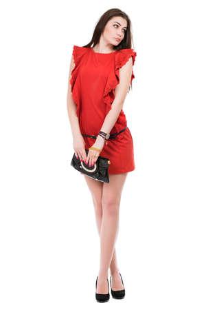 Pretty pensive brunette posing in short red dress. Isolated on white