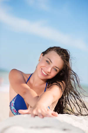 Cheerful sexy brunette posing on the beach photo
