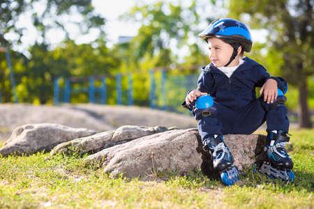 skater boy: Cute little skater boy resting on the stone in the park Stock Photo