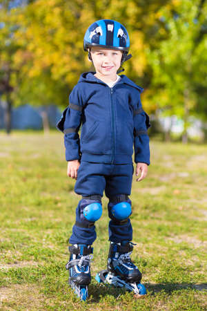 boy skater: Smiling little skater boy in blue sportswear posing outdoors