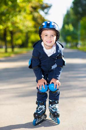 skating fun: Smiling little boy rollerblading down the sidewalk
