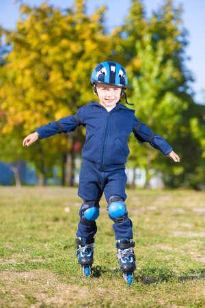 niño en patines: Niño lindo posando sobre patines al aire libre Foto de archivo