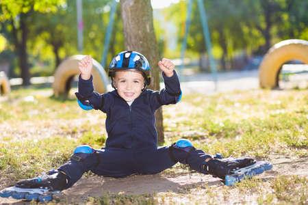 skater boy: Cheerful skater boy in helmet sitting under the tree