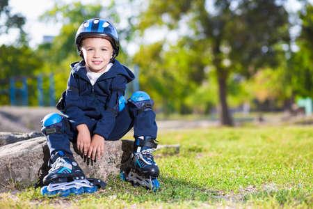 skater boy: Smiling skater boy sitting on the stone in the park