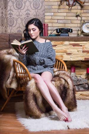 sueteres: Mujer bonita descalzo sentado en la silla y leyendo un libro