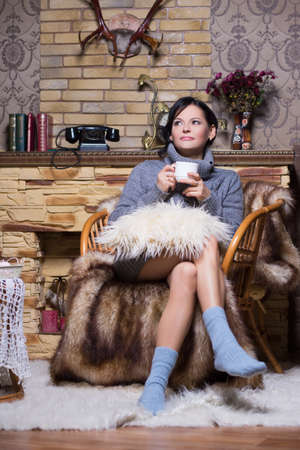 Thoughtful woman in grey sweater and socks sitting on the chair with a cup