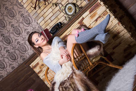 gaiters: Sexy brunette in grey stockings sitting on the chair near a fireplace