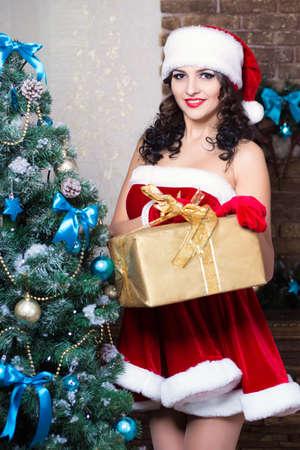 santa's helper: Sexy young woman posing with a gift box wearing like Santa`s helper