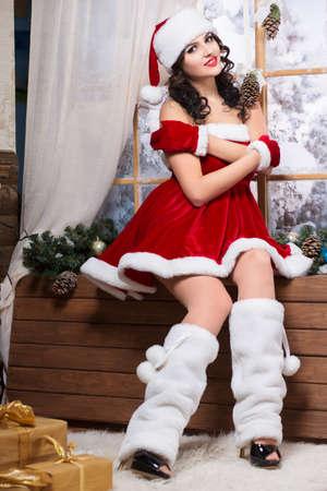 santa's helper: Sexy woman posing on the windowsill wearing like Santa`s helper