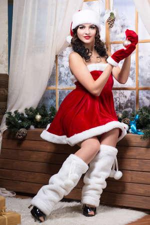 santa's helper: Woman wearing like Santa`s helper posing with christmas toy near the window