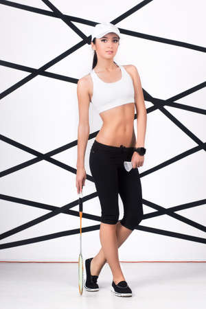 slinky: Young sporty woman in white top and black leggings posing with badminton racket Stock Photo