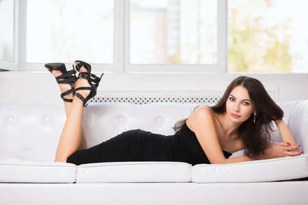 fitting in: Attractive young woman in black fitting dress posing on the sofa