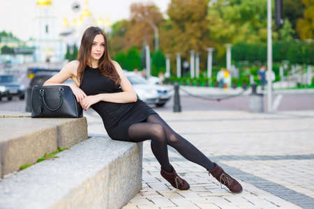 leggy girl: Attractive young brunette wearing black dress posing near the road Stock Photo