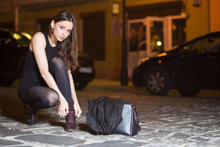 Sexy giovane bruna che indossa un abito nero che si siede vicino alla strada Archivio Fotografico