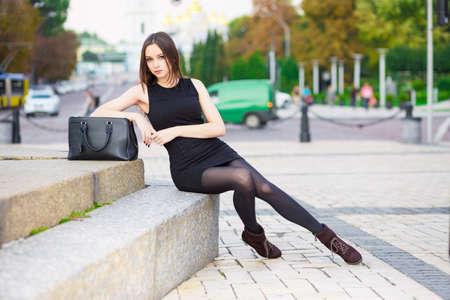 Beautiful young brunette wearing black dress posing near the road