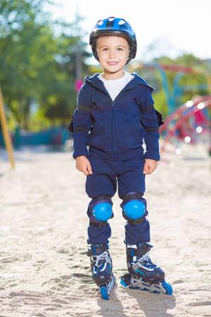 skater boy: Cheerful skater boy in helmet posing on the playground