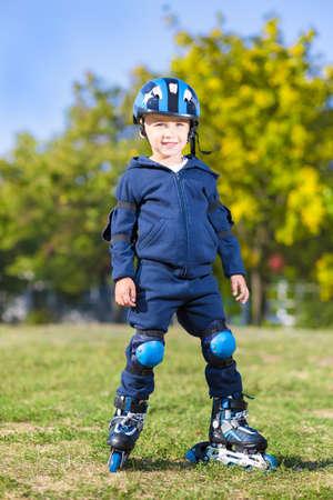 niño en patines: muchacho alegre linda que presenta en patines al aire libre