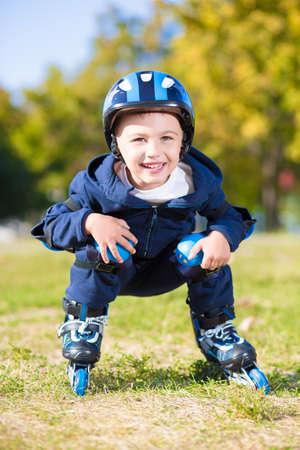 en cuclillas: Alegre pequeño niño de conducción sobre patines en cuclillas Foto de archivo