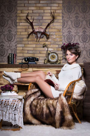 Sexy woman in white socks and sweater posing on the chair with a book Фото со стока