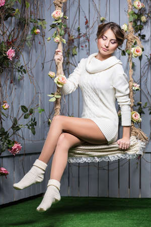 swings: Beautiful young woman in white sweater and socks sitting on a swing Stock Photo