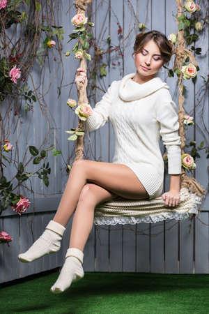 columpios: Hermosa mujer joven en el suéter blanco y medias sentada en un columpio