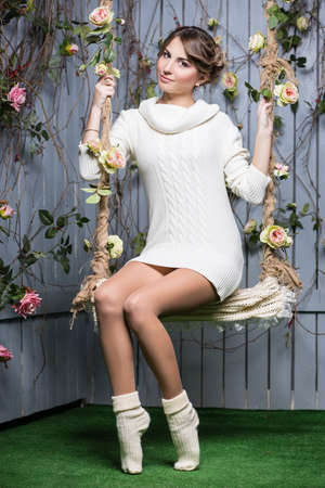 white clothing: Sexy young woman in white sweater and socks posing on a swing
