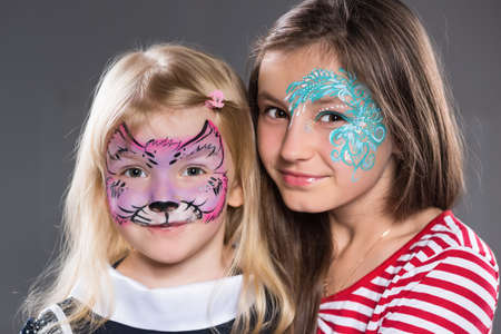 Two girls with painted faces posing indoors