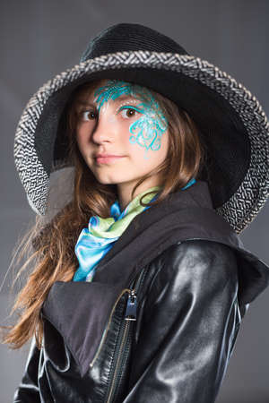 Young girl in black hat and jacket posing with painted face