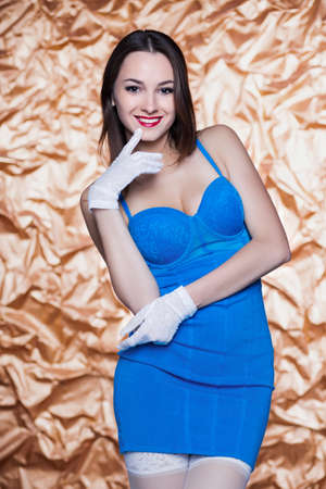 short gloves: Portrait of young smiling woman posing in blue dress and white gloves