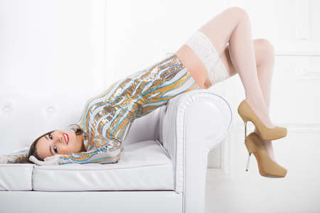 Young smiling woman wearing frank dress and white stockings posing on the sofa