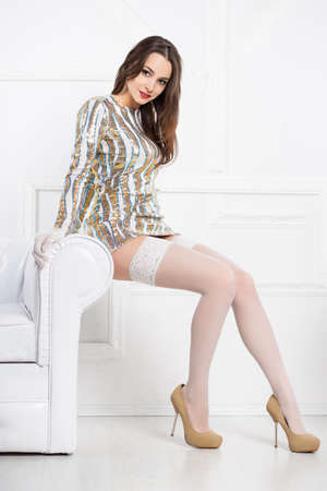 frank: Young sexy brunette wearing frank dress and white stockings posing near sofa