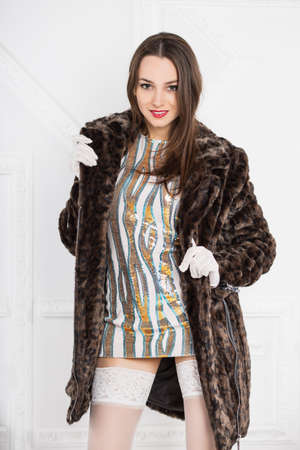 short gloves: Portrait of young sexy brunette posing in short dress and fur coat